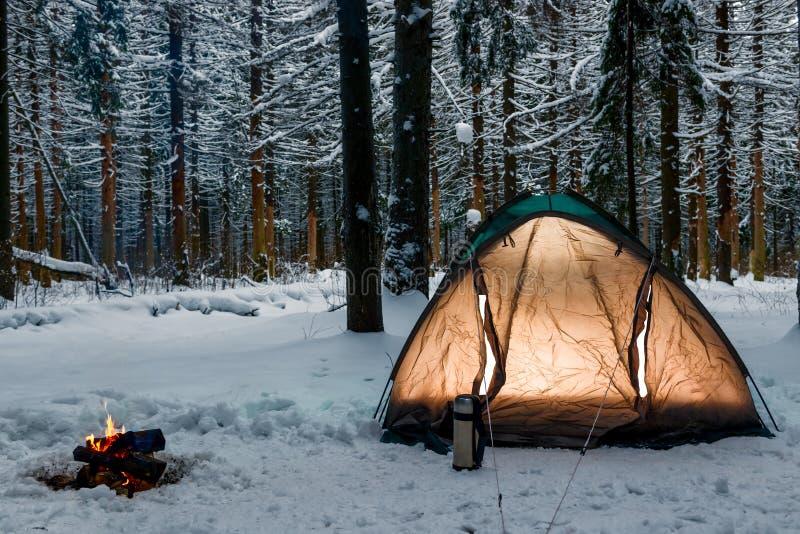 Le feu brûlant près d'une tente dans un camp en hiver images libres de droits