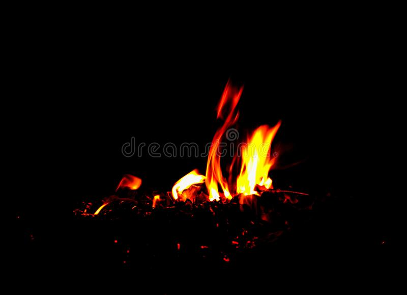 Le feu brûle des feuilles brûlantes dans l'obscurité photo libre de droits