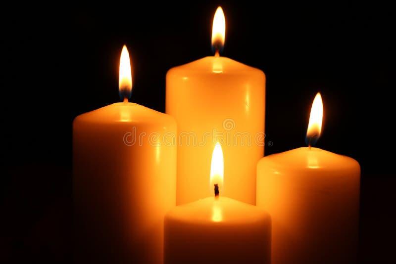 Le feu d'obscurité de quatre bougies images stock
