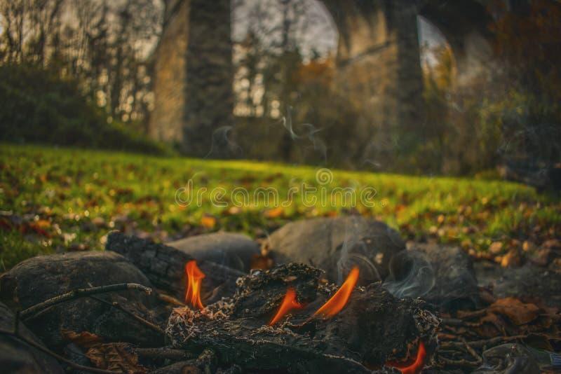 Le feu dans l'extérieur du feu ouvert de montagnes de l'Ecosse dans la forêt près du camping historique de monument photos libres de droits