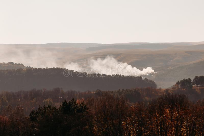 Le feu dans la forêt dans le terrain accidenté en automne photos stock