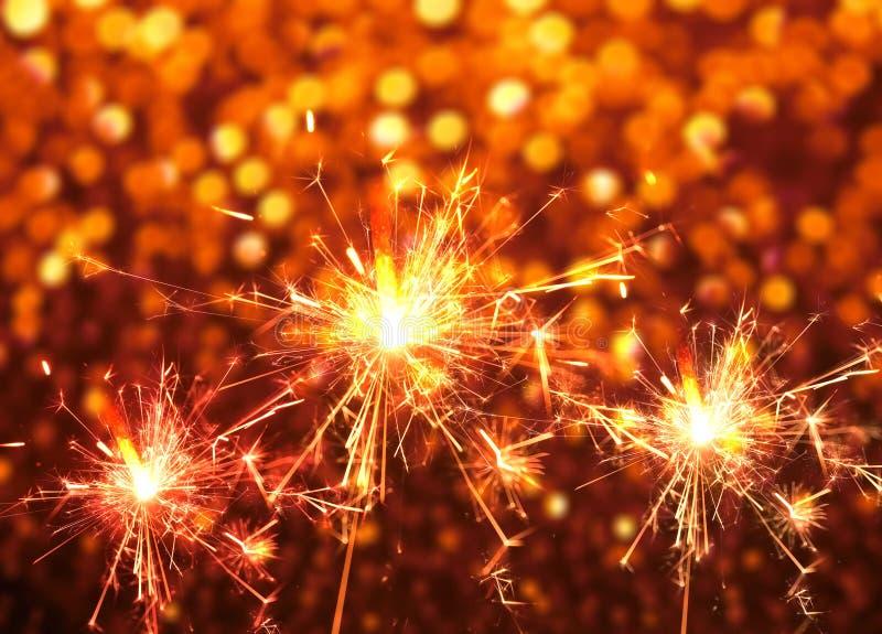 Le feu de cierge magique sur l'abrégé sur rouge bokeh Fond de Noël photo libre de droits