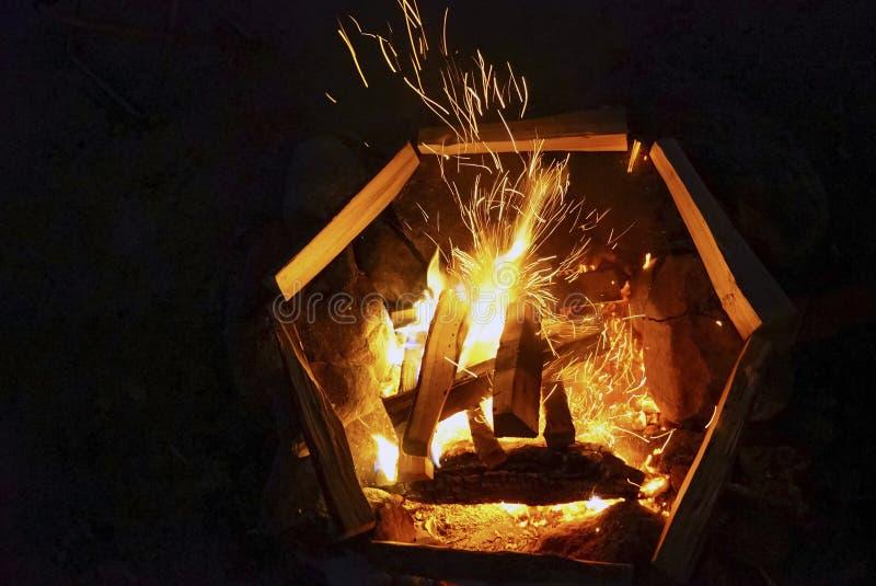 Le feu de scintillement dans le feu avec du bois la nuit sur un fond noir photo libre de droits