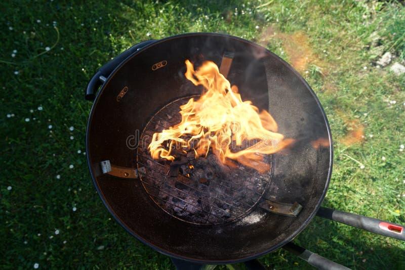 Le feu ouvert dans le gril pour griller une saucisse avec un charbon de bois image libre de droits