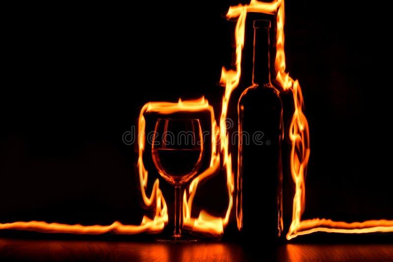 Le feu trace autour de la bouteille en verre et de vin photographie stock libre de droits