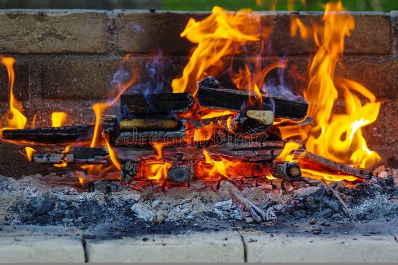 Le fiamme su un barbecue grigliano con il lotto di carbone immagine stock