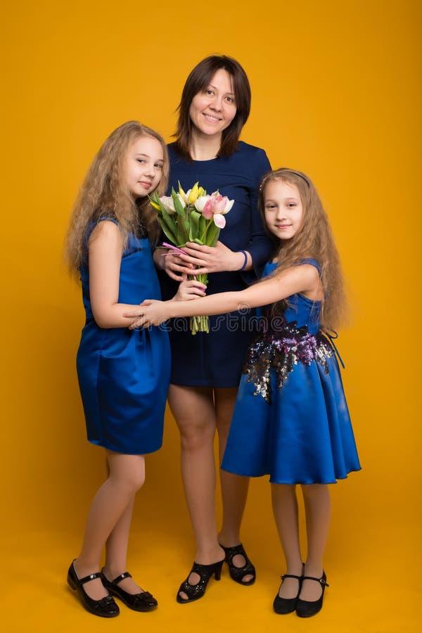 Le figlie augurano a mamma un mazzo felice di festa dei fiori fotografie stock