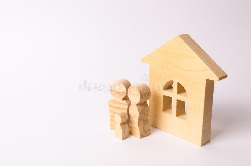 Le figure della gente stanno vicino ad una casa di legno su un fondo bianco Una giovane famiglia sta stando vicino alla loro casa immagini stock