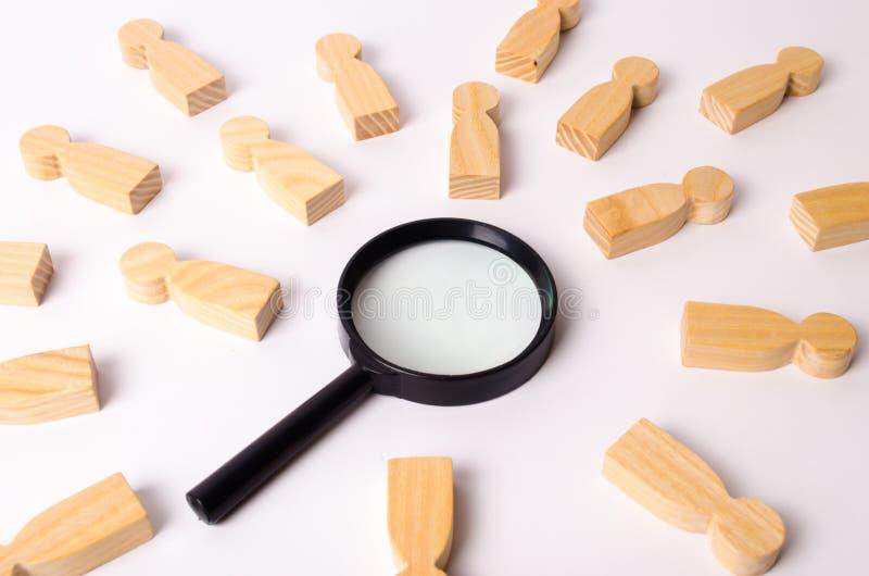 Le figure di legno della gente si trovano intorno ad una lente d'ingrandimento su un fondo bianco Il concetto della ricerca della fotografia stock