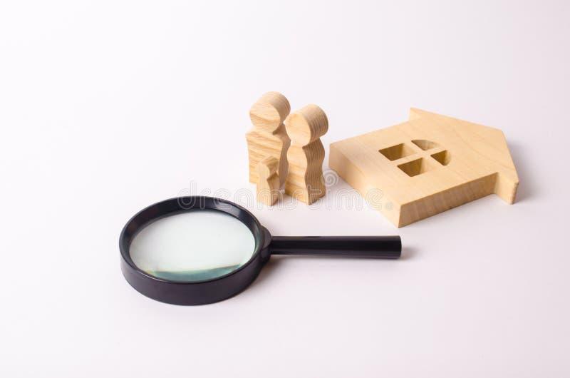 Le figure di legno della gente stanno stando vicino ad una casa di legno e ad una lente d'ingrandimento Il concetto della ricerca immagini stock libere da diritti