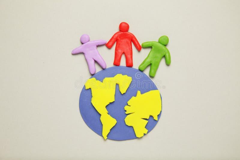 Le figurine della plastilina della gente delle corse differenti sono su pianeta Terra Varie interazioni, comunicazione e globaliz immagini stock