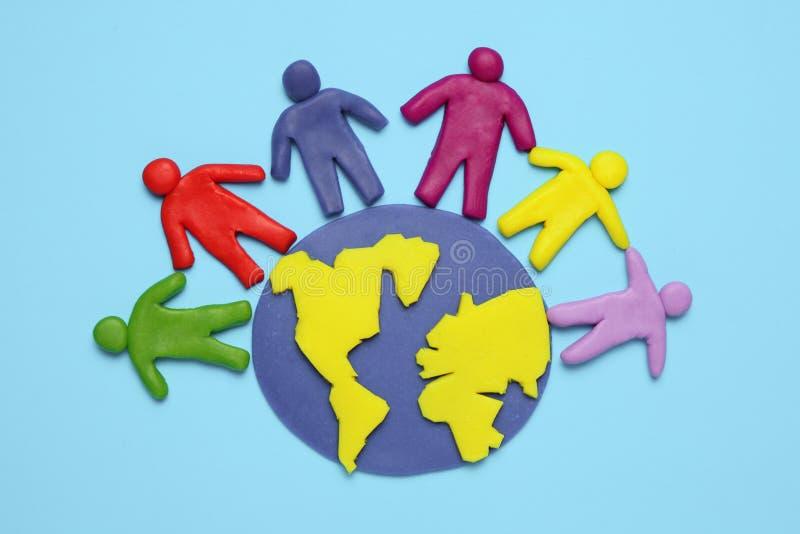 Le figurine della plastilina della gente delle corse differenti sono su pianeta Terra Varie interazioni, comunicazione e globaliz fotografia stock