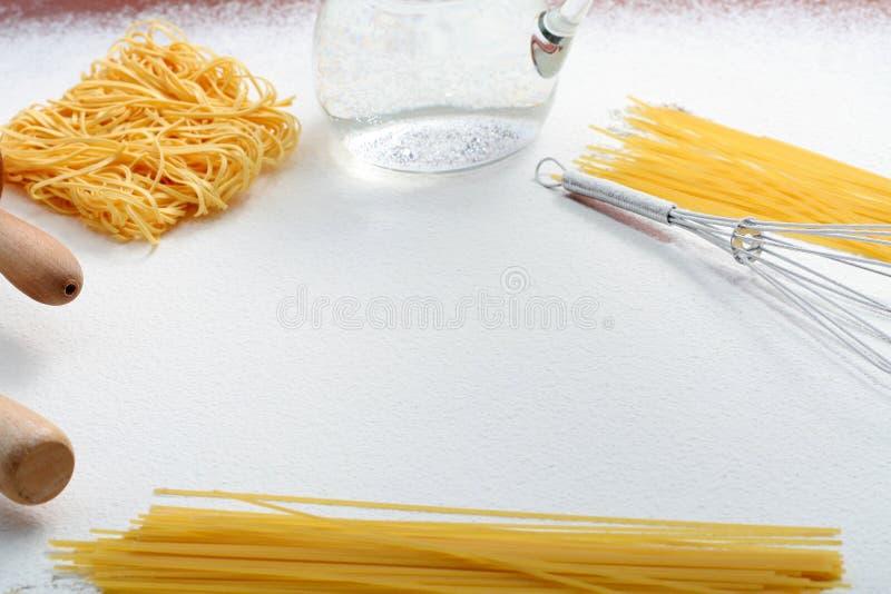 Le fil battent, les macaronis et la goupille sur la farine photographie stock libre de droits