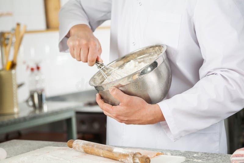 Le fil de Mixing Batter With de chef battent dans la cuvette dedans photographie stock libre de droits
