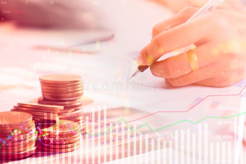 Le file della moneta e dell'uomo d'affari con riferimento al grafico del controllo del mercato azionario vendono fotografia stock libera da diritti