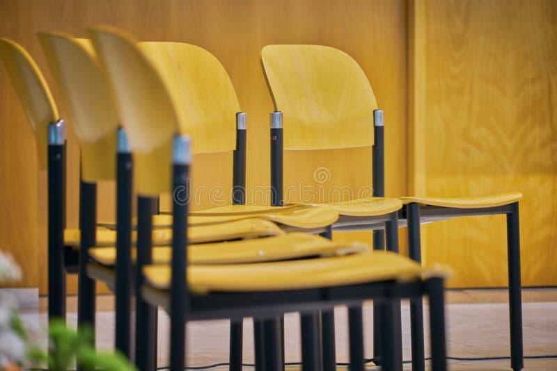 Le file delle sedie vuote hanno preparato per un evento dell'interno Sedie fatte di legno marrone chiaro con la costruzione metal fotografia stock