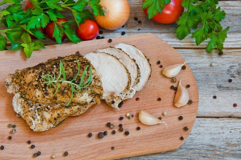 Le filet cuit au four de poulet a coupé sur un panneau de cuisine images stock
