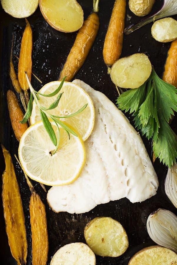 Le filet de morue a fait cuire au four avec les légumes frais du ` s d'agriculteur : pommes de terre, carottes, oignons vue supér photos stock