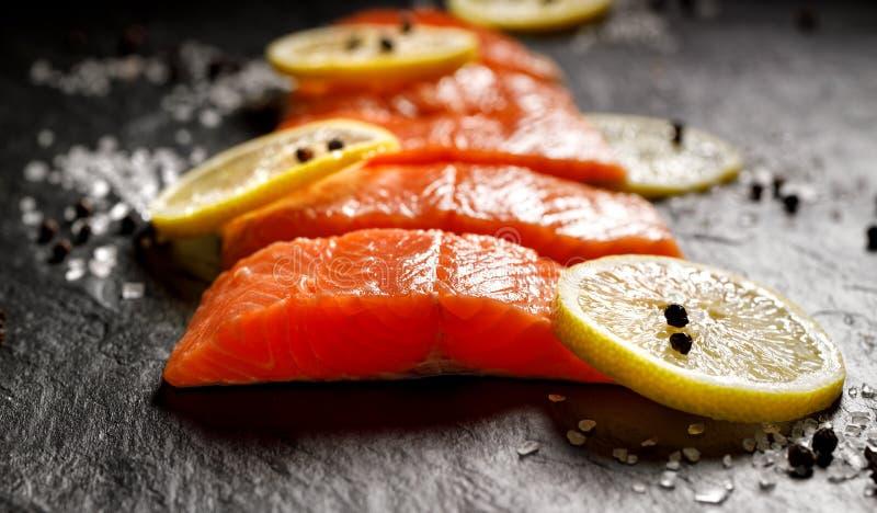 Le filet de poisson frais a coupé en parties avec les tranches, le sel et le poivre de citron sur le fond en pierre noir photos libres de droits