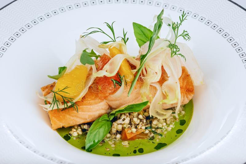 Le filet de poissons rouge saumoné a fait cuire avec le plan rapproché frais de feuilles de salade verte d'isolement du plat blan photo libre de droits
