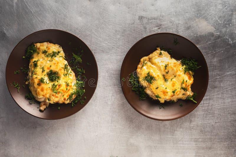le filet de poulet avec l'ananas, a fait dans le four et a complété cuire au four avec du fromage fondu Deux parties images stock
