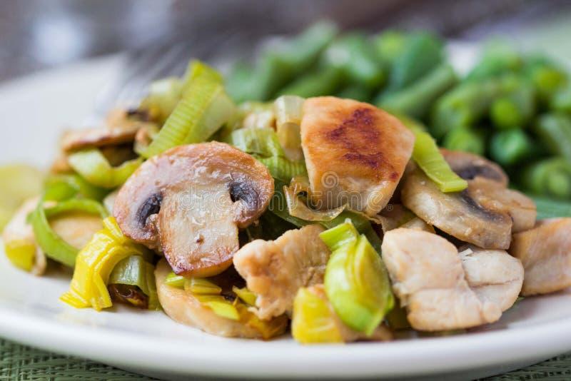 Le filet de poulet a fait frire avec le poireau, champignons, haricots verts, crème images libres de droits