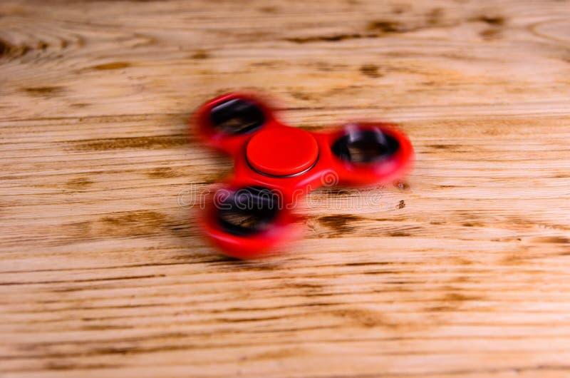 Le fileur rouge de personne remuante tourne sur le bureau en bois photo libre de droits