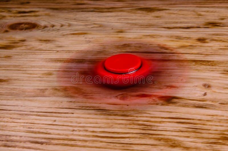 Le fileur rouge de personne remuante tourne sur le bureau en bois images libres de droits