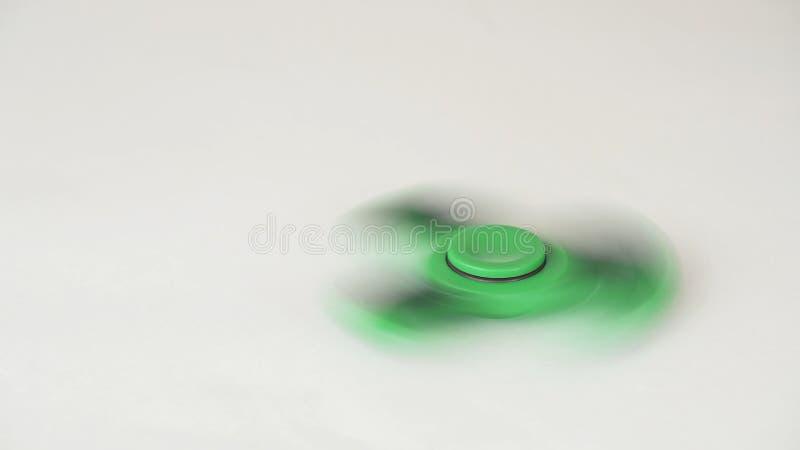 Le fileur vert de personne remuante tourne et s'arrête sur le fond blanc photo stock