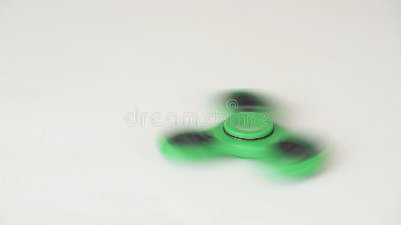 Le fileur vert de personne remuante tourne et s'arrête sur le fond blanc images stock