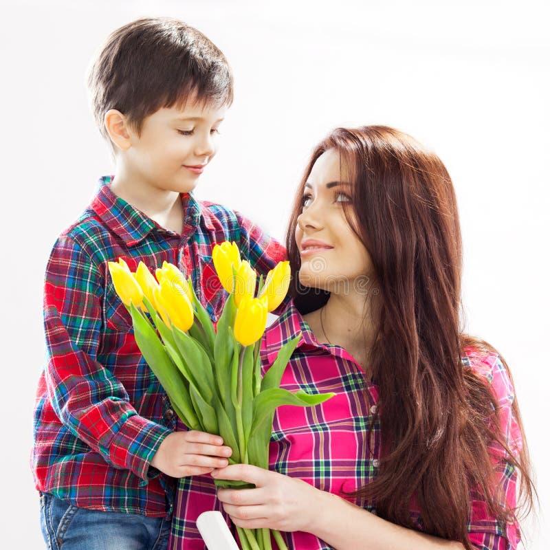 Le fils étreignant sa mère et lui donne des fleurs photo libre de droits