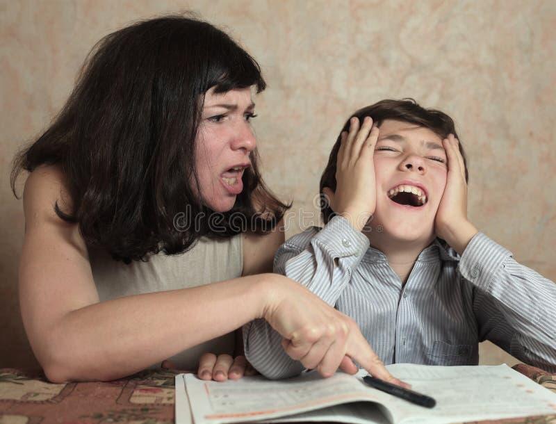 Le fils d'aide de maman font des devoirs de difficul images libres de droits