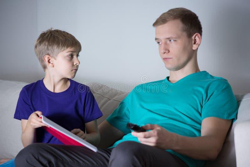 Le fils demande à son père l'aide image stock