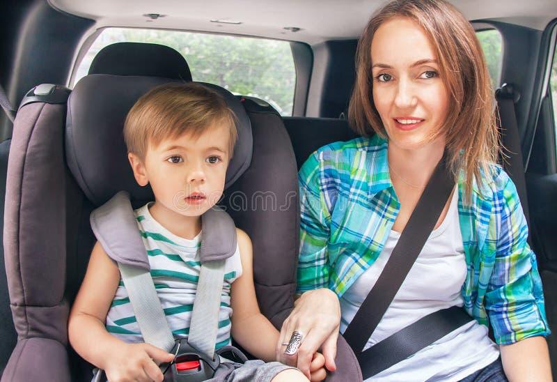 Le fils et la mère mignons caucasiens sont bouclés avec la ceinture de sécurité dans a photographie stock