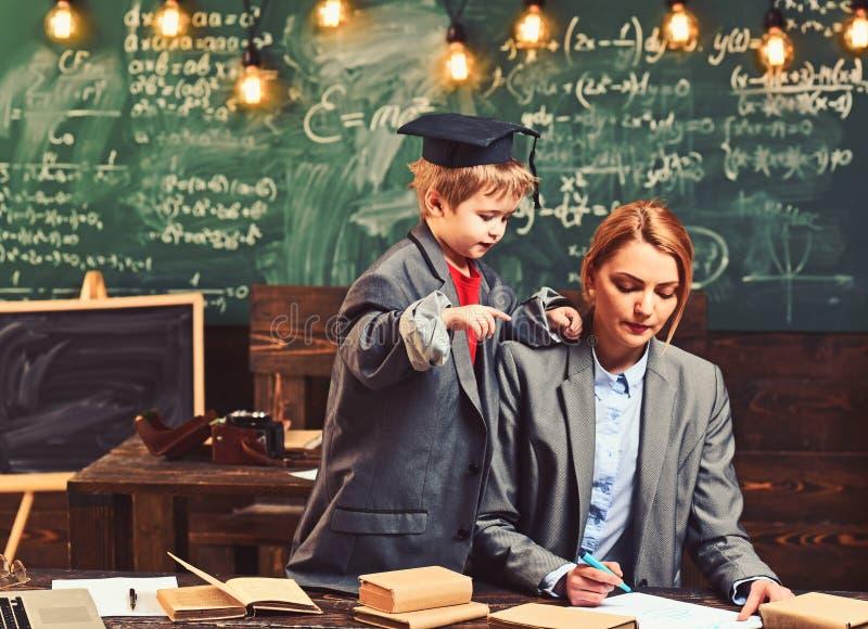 Le fils et la mère ont la leçon d'école Aide de garçon de génie la femme d'écrire des devoirs au bureau Peu enfant dans le grand  images libres de droits