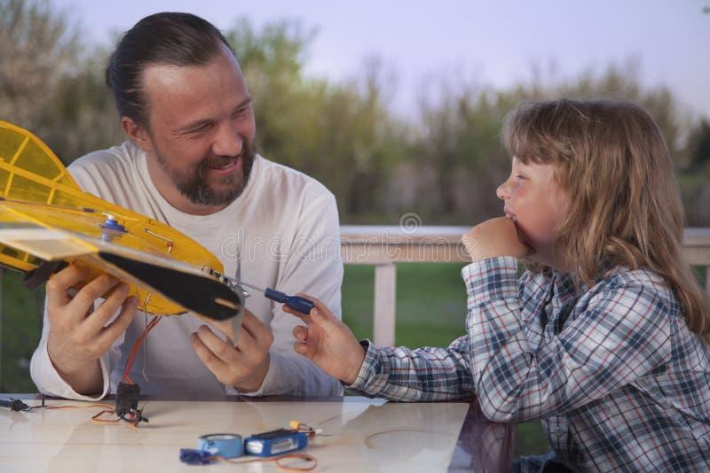 Le fils et le père ont fait les avions modèles radioguidés faits maison AI image libre de droits