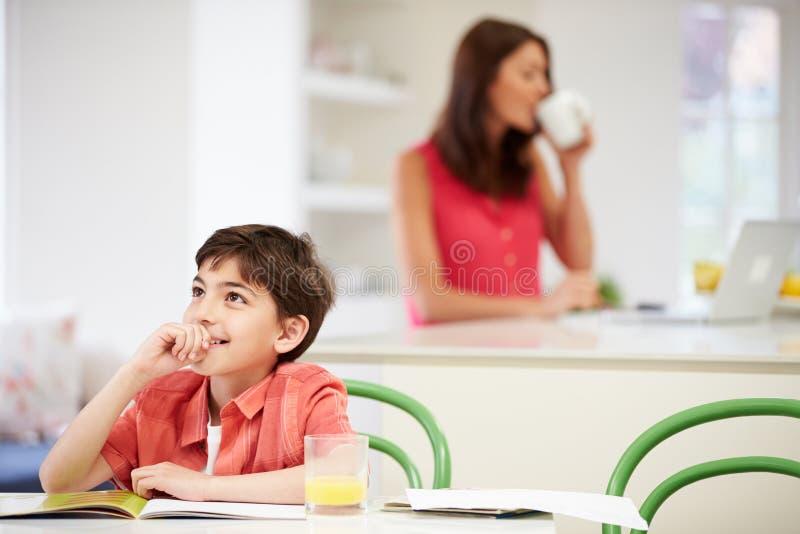 Le fils fait le travail pendant que la mère utilise l'ordinateur portable images stock