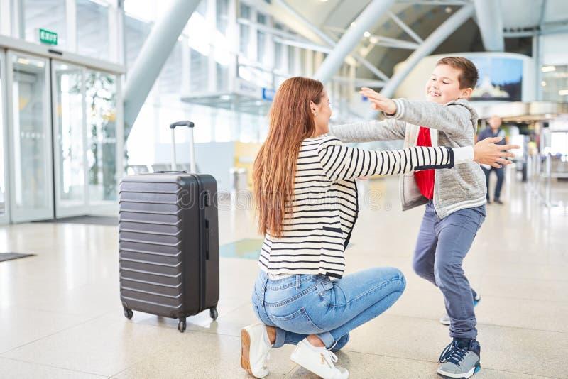 Le fils souhaite la bienvenue à sa mère dans le terminal d'aéroport photos libres de droits