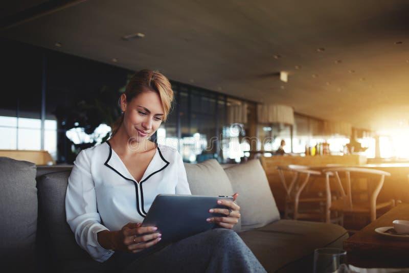 Le financier féminin lit des actualités financières dans l'Internet par l'intermédiaire du pavé tactile pendant la pause en café  image libre de droits