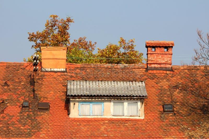 Le finestre del tetto circondate con le piccole mattonelle di tetto ed i camini del mattone rosso accanto al palo arrugginito del fotografie stock