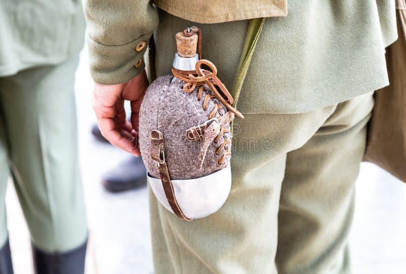 Le flacon militaire de cru accroche sur une ceinture d'un soldat photographie stock libre de droits