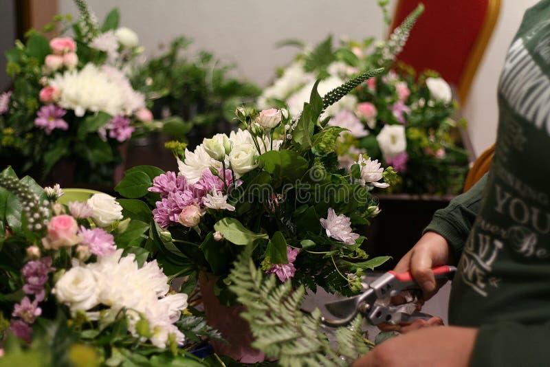 Le fleuriste créant la composition des fleurs photographie stock
