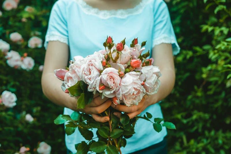 Le fleuriste de jeune femme donne un bouquet des roses pour la livraison image stock