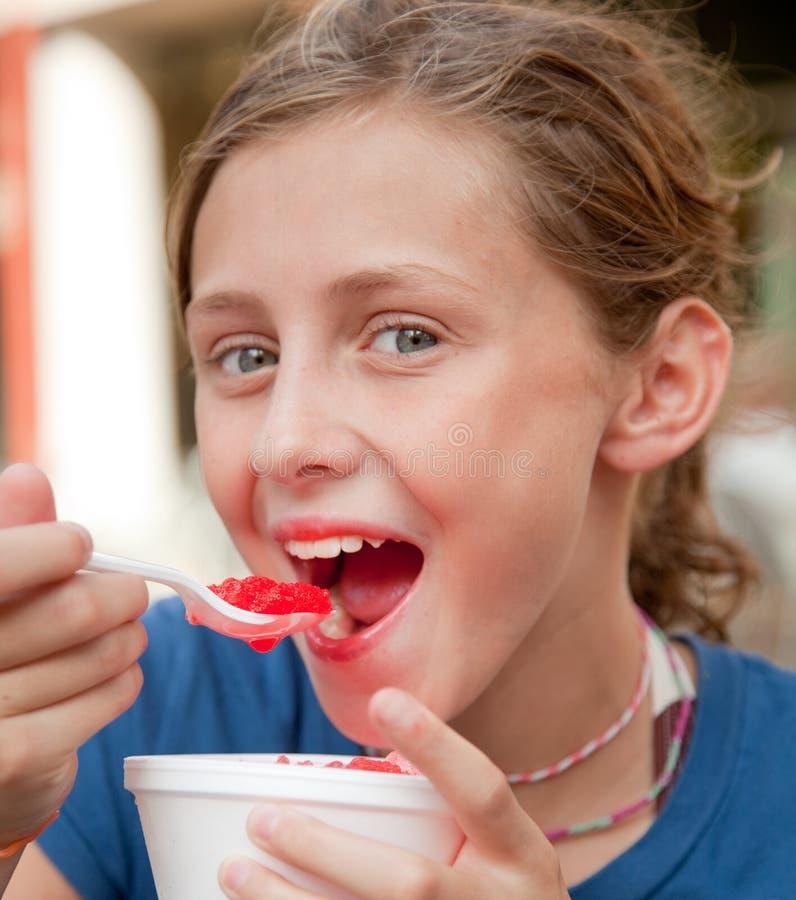 Le flicka som äter en snowkotte arkivbild
