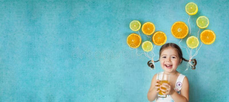Le flickan dricker ny orange fruktsaft arkivfoto