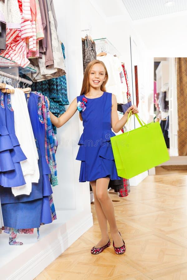 Le flickan i blått klä med shoppingpåsen royaltyfria bilder