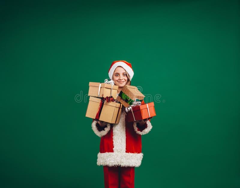 Le flickan i den Santa Claus klänningen som rymmer hennes julgåvor royaltyfri fotografi