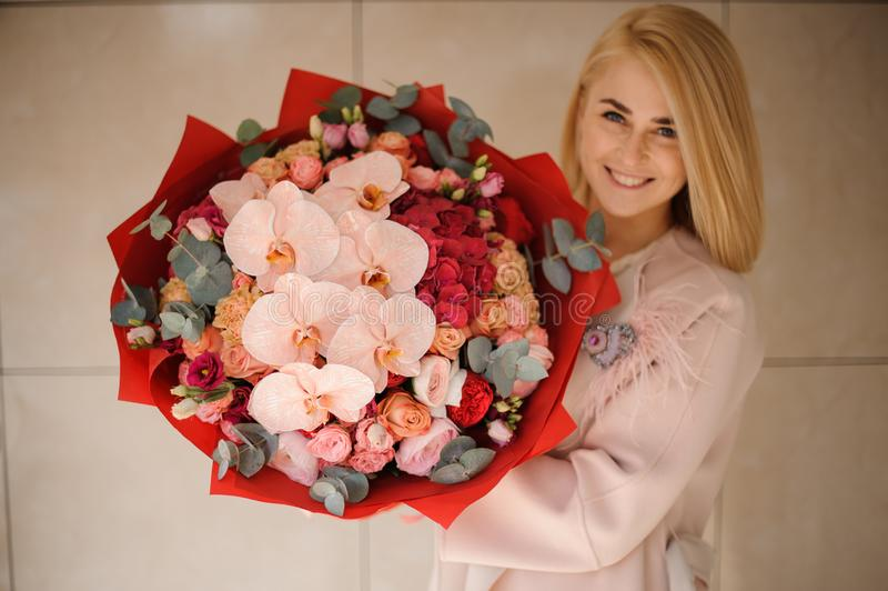 Le flickan i laget som rymmer en bukett av rosa och röda blommor som dekoreras med grönska fotografering för bildbyråer