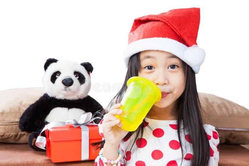 Le flickan i santa hjälpredahatt med nallebjörnen arkivfoto