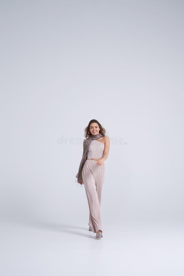 Le flickan i stilfull kläder som går in mot kamera royaltyfria foton